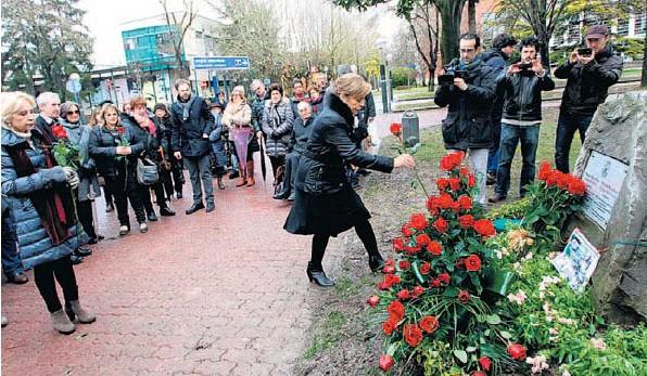 Natividad Rodríguez deposita una rosa ante el monolito. A la izquierda, Begoña Elorza. BLANCA CASTILLO